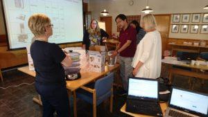 Hverdagsteknologier på bordet i et møterom, omringet av medarbeidere i Vaksdal kommune