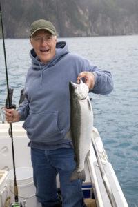 En eldre man som står i båten og viser fram sin store fisk.