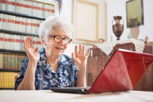 Eldre kvinne med briller foran en dataskjerm. Hun Skyper med sin sønn.