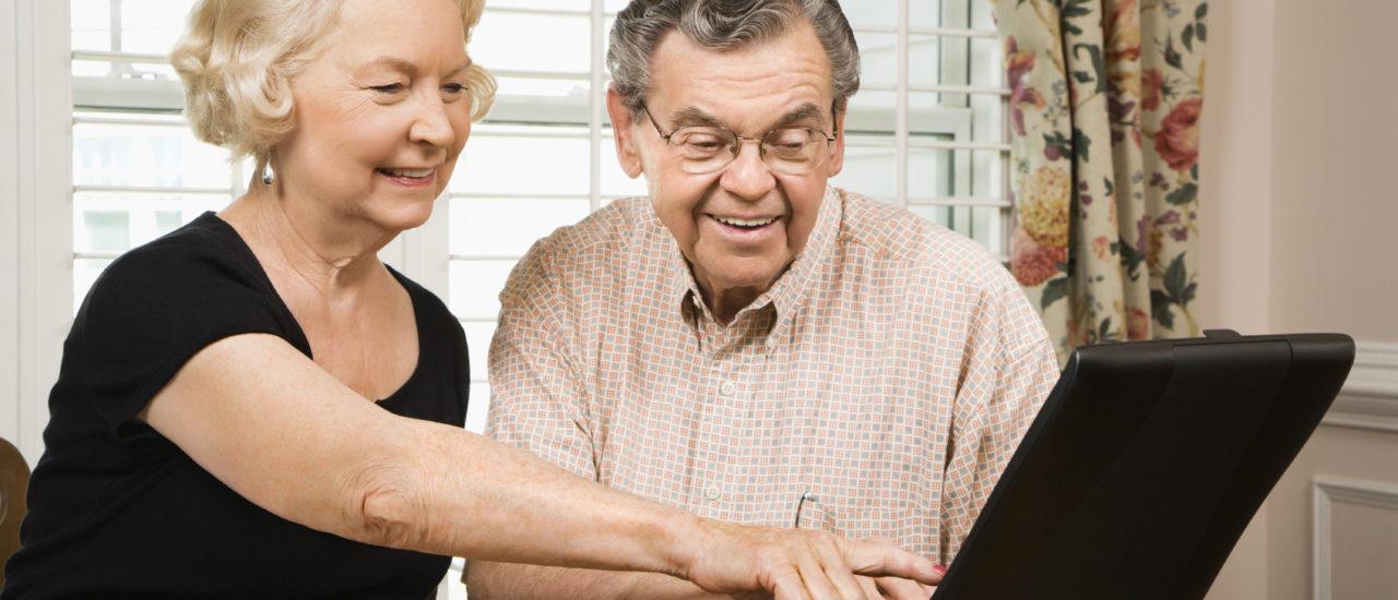 Eldre par ser på PC-skjermen sammen og er glade